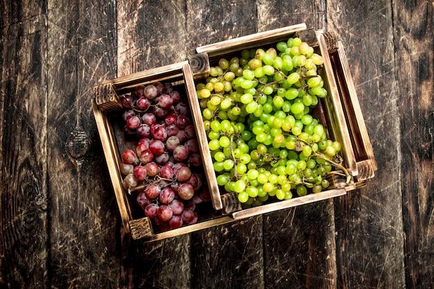 箱に入ったブドウの新鮮な収穫。木製のテーブルの上。