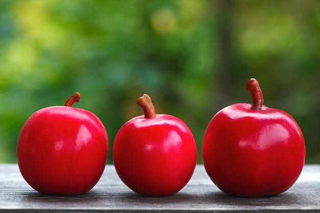 Свежий урожай спелых красных яблок на деревянной поверхности.