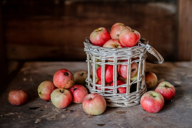 Fresh harvest of ripe and healthy farm apples in a glass jar, in a basket.