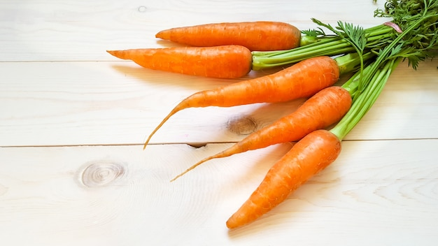 Fresh harvested carrot on wooden table in garden