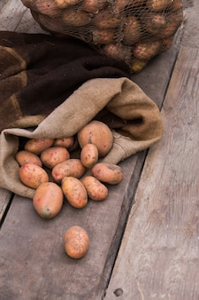 Свежесобранного картофеля с почвой все еще на коже, разлив из мешковины, на грубой деревянной палитре.