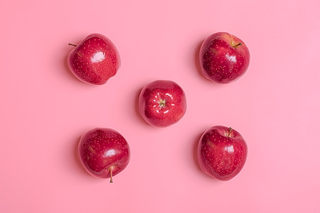 Fresh harvested red apple lies on trend pink millennial background