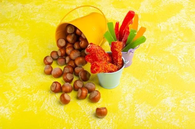 Nocciole fresche insieme a torrone e marmellata su giallo