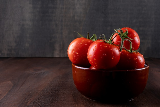 Fresh and health tomatoes in ceramic bowl on brown stone surface