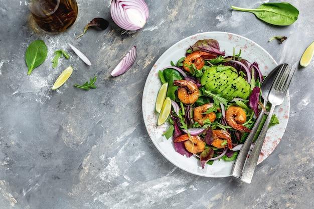 Свежий здоровый салат из авокадо и креветок. концепция морепродуктов. вкусный овощной микс из листьев, креветки на гриле. баннер, место рецепта меню для текста, вид сверху.
