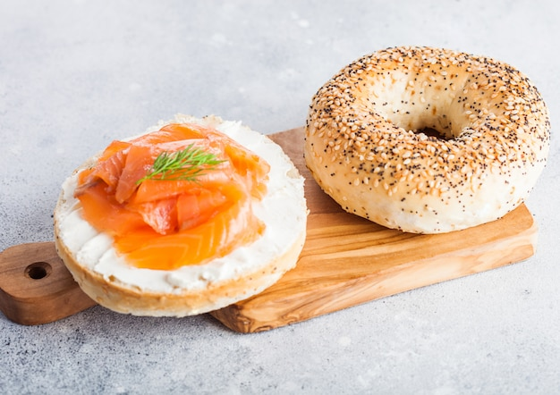 Fresh healthy bagel sandwich with salmon, ricotta and dill on vintage chopping board on light kitchen table.