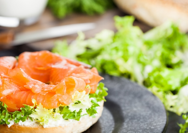 Fresh healthy bagel sandwich with salmon, ricotta and soft egg on vintage chopping board on white kitchen table