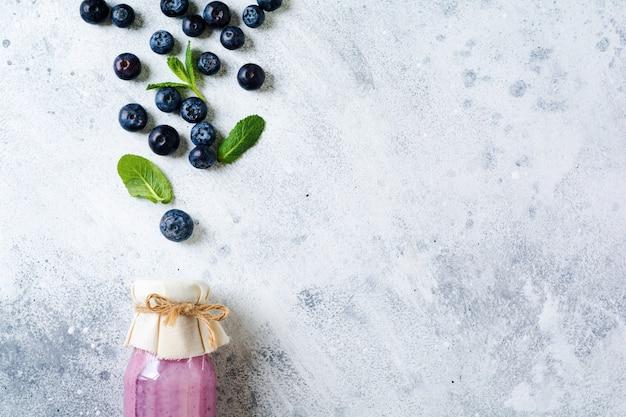 신선한 건강 한 블루 베리 스무디 딸기와 밝은 흰색 콘크리트 표면에 유리 항아리에 민트. 제로 폐기물 개념 .top 뷰