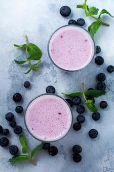 Свежие здоровые ягоды смузи черники и мята в стакане на светлой белой бетонной поверхности