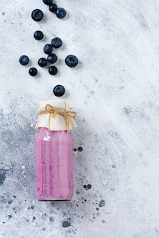Fresh healthy blueberries smoothie berries and mint in glass jar on light white concrete background.