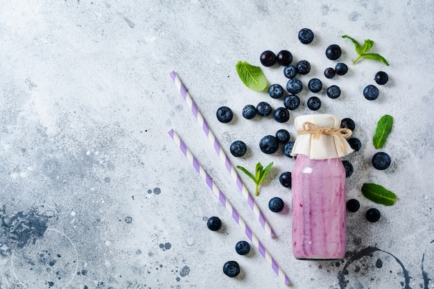 Fresh healthy blueberries smoothie berries and mint in glass jar on light white concrete surface. zero waste concept .top view