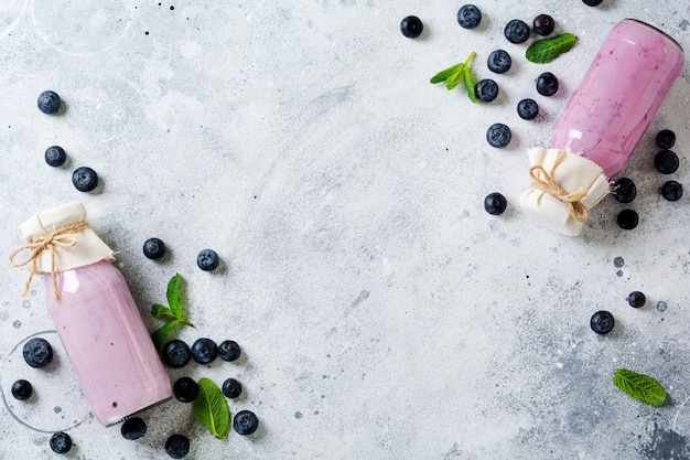 Fresh healthy blueberries smoothie berries and mint in glass jar on light white concrete surface