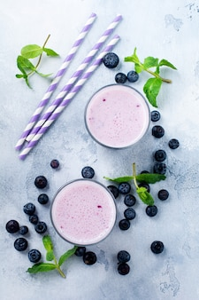 Fresh healthy blueberries smoothie berries and mint in glass on light white concrete background.