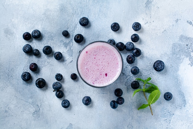Fresh healthy blueberries smoothie berries and mint in glass on light white concrete background