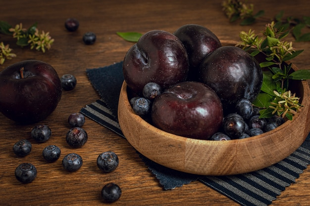 Fresh healthy bowl full of plums and blueberries