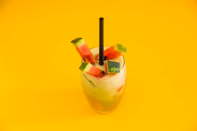 Fresh healthy cocktail with watermelon slice on yellow backdrop