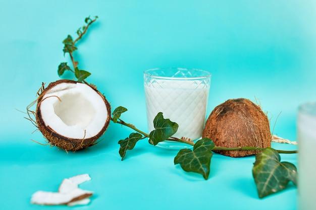 Свежее здоровое кокосовое молоко в стакане на голубой стене, альтернативный тип веганского молока, концепция органического здорового напитка.