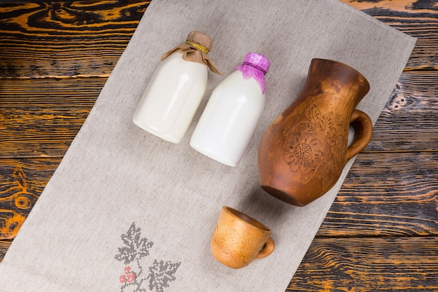 陶器の水差しとカップ、俯瞰図と素朴な木製のテーブルの上の布の上に配置されたボトルの新鮮な健康的な農場の牛乳