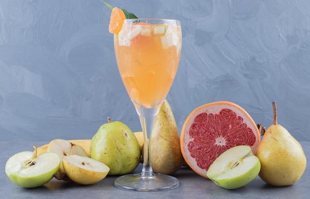Свежий здоровый фруктовый сок на сером фоне с сезонными фруктами.