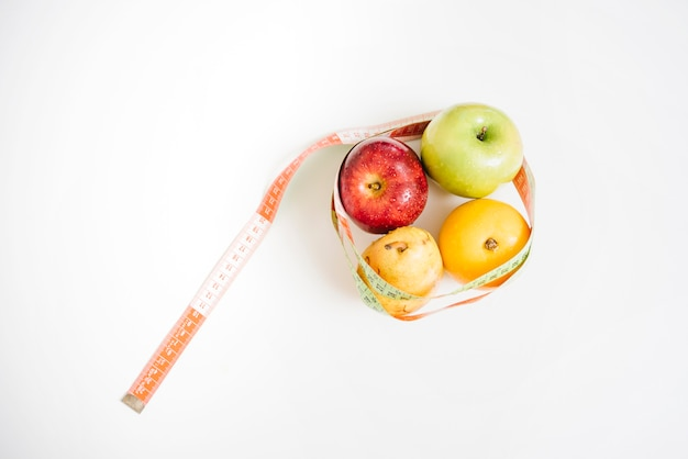 Fresh healthy fruits covered with measuring tape