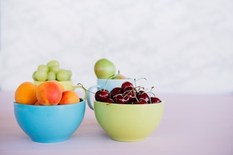 Fresh healthy fruits in bowl on white surface