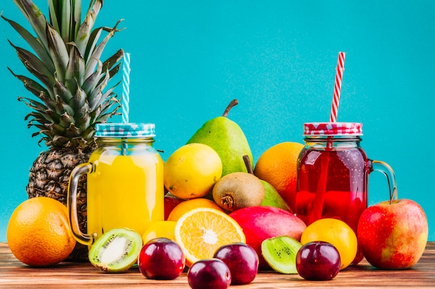 Fresh healthy fruits and juice mason jars on table against blue background