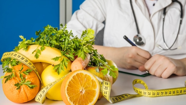 Fresh healthy fruits with measuring tape on dietician's desk