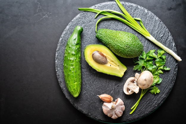 Fresh healthy green food still life with a flat lay arrangement of avocado pear, spring onion, garlic, parsley and cucumber on a round black board
