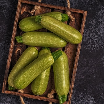 Fresh healthy green zucchini courgettes in brown wooden box
