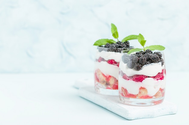 Fresh healthy multilayered dessert trifle with raspberries, blackberries on pastel blue background