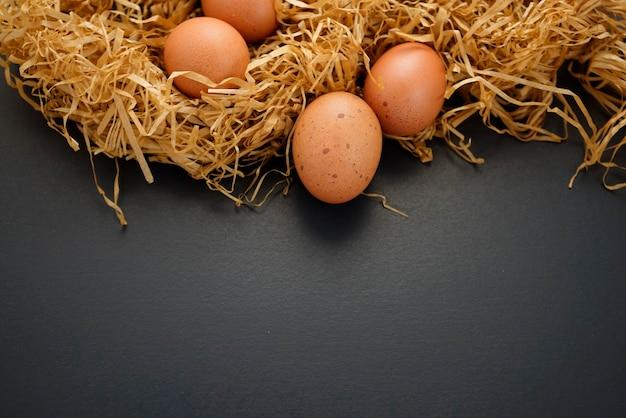 Свежие здоровые органические крапчатые коричневые яйца без сена с плоской кладкой сена на черном фоне