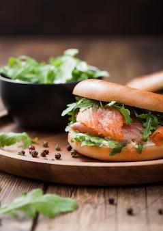 Свежий здоровый органический бутерброд с лососем и бубликом, сливочным сыром и дикой ракеты в тарелке на деревянном фоне.