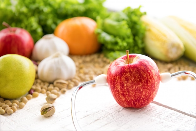 Fresh healthy red apple wearing stethoscope on white wood table