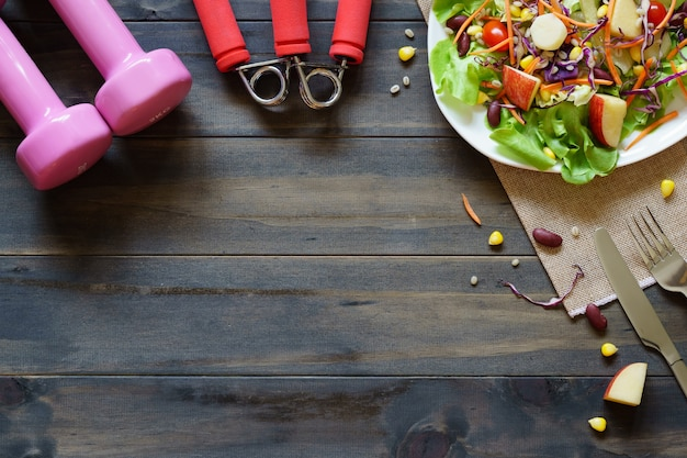 Fresh healthy salad with dumbbells and excercise equipment on wood background