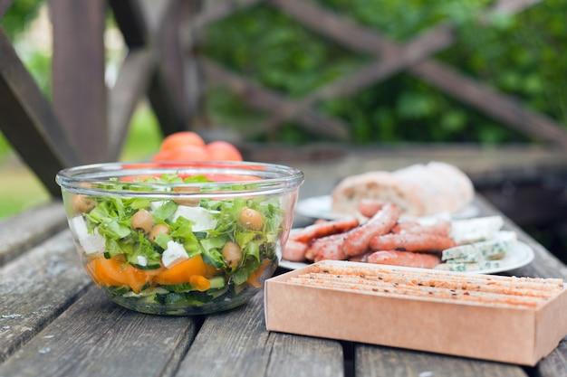 나무 테이블에 있는 큰 그릇에 올리브와 죽은 태아의 치즈를 곁들인 신선한 건강 샐러드. 피크닉 시간에 구운 쿠키, 소시지와 빵. 맛있는 신선한 음식