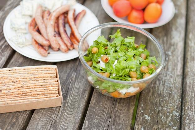 나무 테이블에 올리브와 죽은 태아의 치즈를 곁들인 신선한 건강 샐러드. 피크닉 시간에 소시지와 함께 구운 칩. 맛있는 신선한 음식