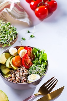 Fresh healthy salad with quinoa, cherry tomatoes and mixed greens, avocado, egg and micro greens on marble