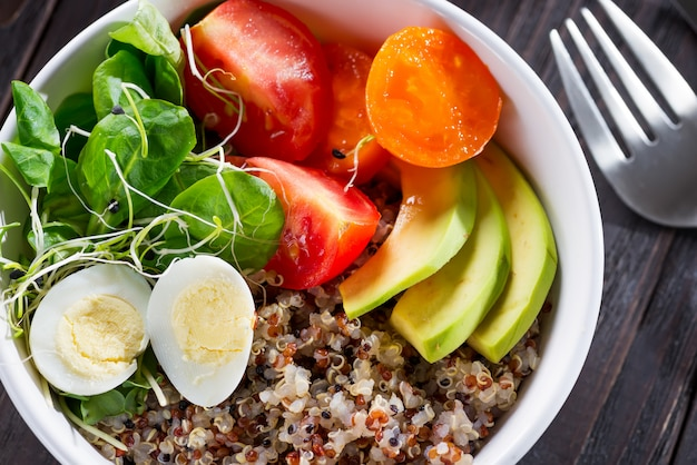 Fresh healthy salad with quinoa, cherry tomatoes and mixed greens, avocado, egg and micro greens on wood