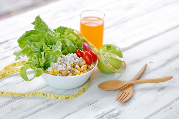 Fresh healthy salad with tape measure on the table. fitness and health concept.