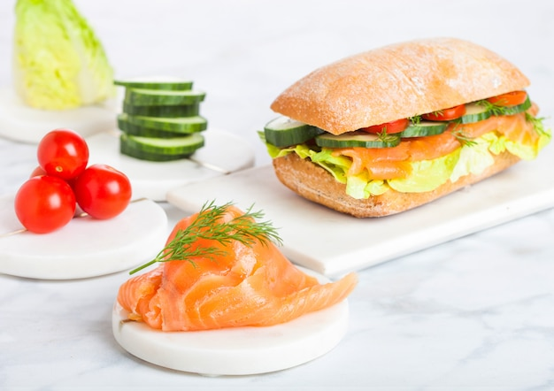 Fresh healthy salmon sandwich with lettuce and cucumber and tomatoes on marble board.diet healthy food