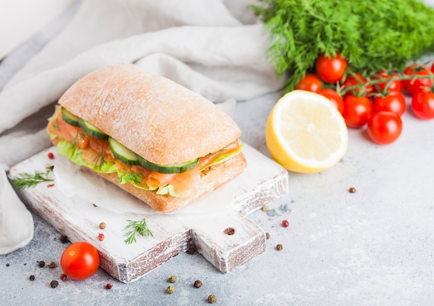 Fresh healthy salmon sandwich with lettuce and cucumber on vintage chopping board. breakfast snack. fresh tomatoes, dill and lemon.