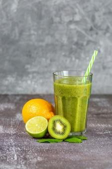 Свежий здоровый коктейль в высоком стеклянном стакане с соломинкой в окружении фруктов на сером фоне бетона. понятие о правильном питании, похудании, детоксикации организма.