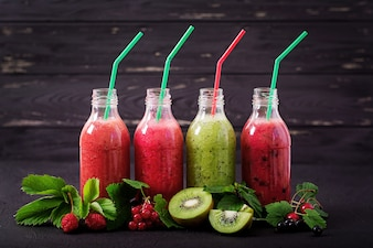 Fresh healthy smoothies from different berries on a dark background. Diet menu.