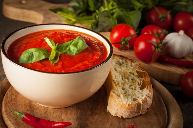 Fresh, healthy tomato soup with basil, pepper, garlic, tomatoes and bread. spanish gazpacho soup.