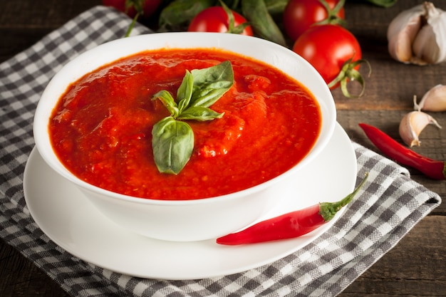 Fresh, healthy tomato soup with basil, tomatoes on wooden background. spanish gazpacho soup.