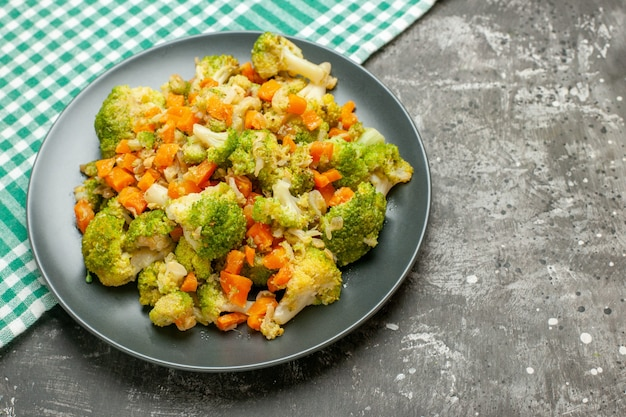 Insalata di verdure fresca e sana sul tovagliolo spogliato verde sulla tavola grigia