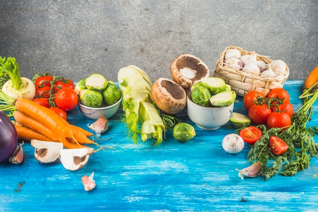 Fresh healthy vegetables on blue wooden tabletop
