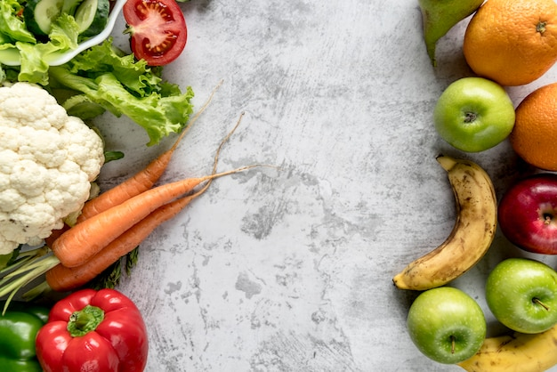 Fresh healthy vegetables and fruits over concrete backdrop