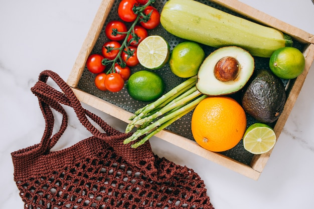 Fresh healthy vegetables in wooden box and eco shopping bag on white marble background