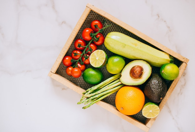 Fresh healthy vegetables in wooden box on white marble background